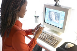 Young woman takes notes at a computer about the 6-traits Voice trait